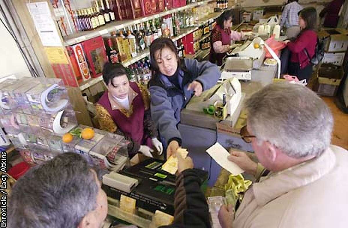 Tai Muiung and Mabele Vogt, work the register as early buyers purchase their lottery tickets at Kum Luen Market, for the big pay off Lotto on Wed. in Chinatown, Tuesday Feb.13,02. CHRONICLE PHOTOGRAPHER/ LACY ATKINS