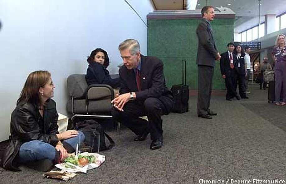 Governor Gray Davis stops to talk to Jennifer Grace, SF, at SFO as she sits on the floor eating a salad. During a stop at San Francisco International Airport Gov Davis has called for Americans to travel and to announce that National Guard will provide security at airports. CHRONICLE PHOTO BY DEANNE FITZMAURICE Photo: DEANNE FITZMAURICE
