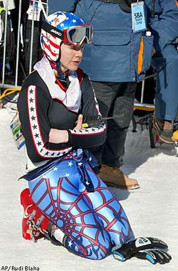 Jonna Mendes of the United States kneels down in the mixed zone at the finish area after finishing her Women's Downhill training run in Snowbasin, Utah Sunday Feb. 10, 2002. (AP Photo/Rudi Blaha) Photo: RUDI BLAHA