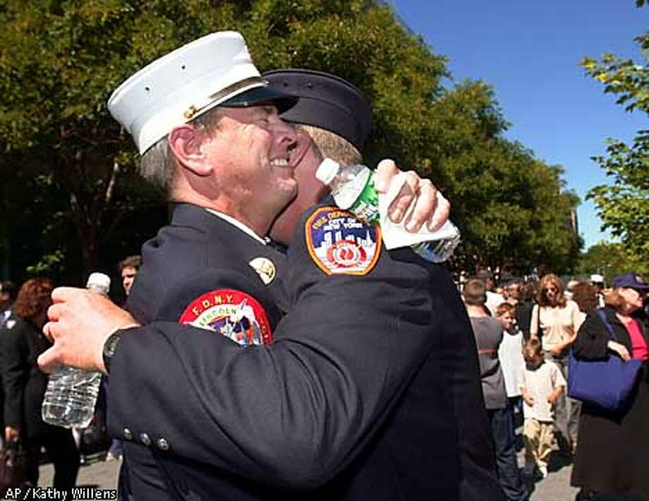 New York City Fire Batallion 39 Chief Bob Keys, left, embraces his brother Tim, who was promoted, following a promotion ceremony to replace fire department personnel killed in the World Trade Center terrorist attacks, Sunday, Sept. 16, 2001, in the Brooklyn borough of New York. The Fire Department's chief and hundreds of firefighters were lost in the attacks and the subsequent collapse of the World Trade Center towers. (AP Photo/Kathy Willens) Photo: KATHY WILLENS