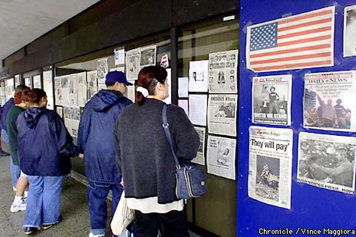 People looking at news papers on the World Trade Center on walls at the Jersey Journal Square in Jersey City. Days after the terrorist attack on the World Trade Center in New York BY Vince Maggiora