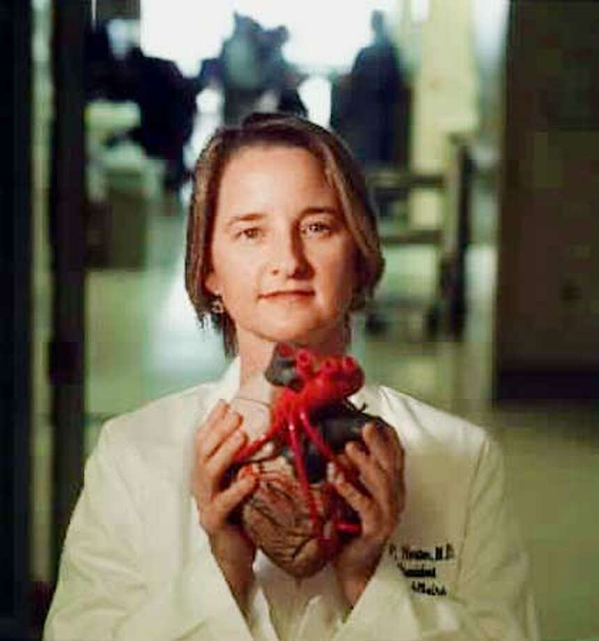 Darlene Horton, shown here holding a heart model, led a team who designed an experiment to prove to the FDA that Natrecor is safe. Chronicle photo by Eric Luse