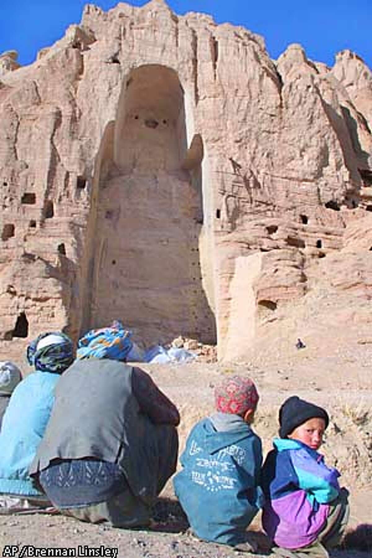 Afghan villagers sit near the hole left behind after an enormous Buddha statue was destroyed by the former Taliban regime, in Bamiyan, northern Afghanistan, Wednesday, Jan. 2, 2002. The Buddha statues detroyed by the Taliban were part of a large network of smaller temples built right into the side of the mountain around one-thousand five-hundred years ago, when Bamiyan played a central role in the region's east-West trade route. The extremist view, not shared among most Islamic scholars but acted upon by the Taliban, held that the Buddha statues very existence violated the Islamic code forbidding idolatry. (AP Photo/Brennan Linsley)
