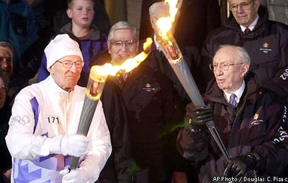 Gordon B. Hinckley, right, president of the Mormon church, lights the torch of Neal A. Maxwell on Thursday, Feb. 7, 2002, in Salt Lake City. Maxwell is a member of the church's Quorum of the Twelve. (AP Photo/Douglas C. Pizac) Photo: DOUGLAS C. PIZAC
