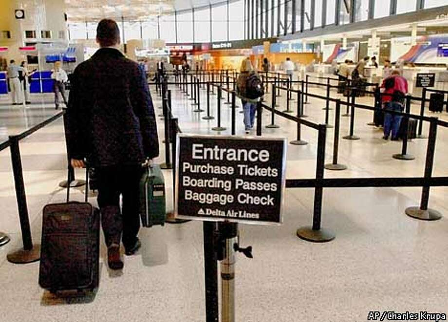 Passengers walk through the nearly empty baggage and ticketing corrals at Delta Airlines at Boston's Logan Airport, Monday morning Sept. 24, 2001. While most workers return to start a new week with their normal commuting routines, air travel for business has been sparce. Some commuters arriving in Boston said that their flights, which were in the past were full on Monday mornings, had only a third of their plane filled. (AP Photo/Charles Krupa) Photo: CHARLES KRUPA