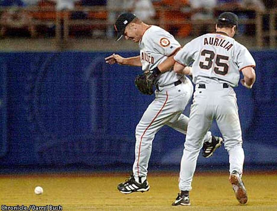 Giants Jeff Kent, left, and Rich Aurilia collide as they cant reach a short fly ball hit by Dodger Mark Grudzielanek in the Dodger seven run 6th inning at Los Angeles. Chronicle photo by Darryl Bush Photo: Darryl Bush