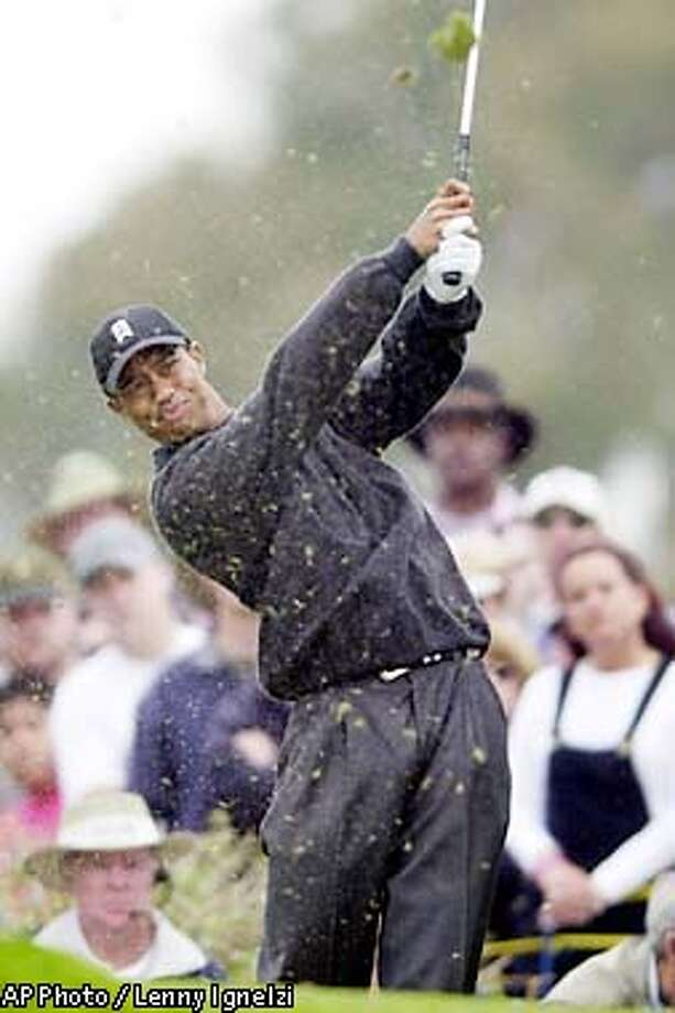 Tiger Woods sends the turf flying as he hits his tee shot on the par three third hole of the South Course at Torrey Pines during the second round of the Buick Invitational Friday, Feb.8, 2002, in San Diego. Woods hit his shot into the canyon adjacent the green and made double bogey. (AP Photo/Lenny Ignelzi) Photo: LENNY IGNELZI