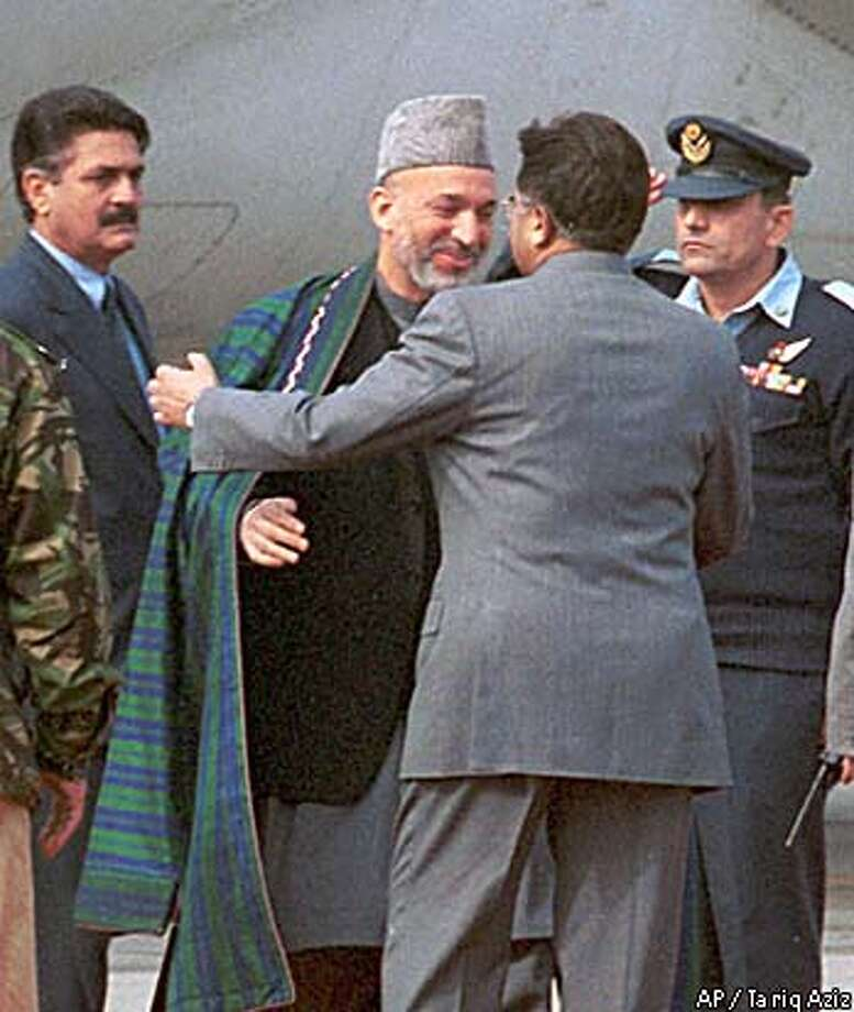 "On a visit to Pakistan, Afghan interim leader Hamid Karzai (center left) was greeted by President Pervez Musharraf. They agreed to bury past ""misunderstandings."" Associated Press photo by Tariq Aziz"
