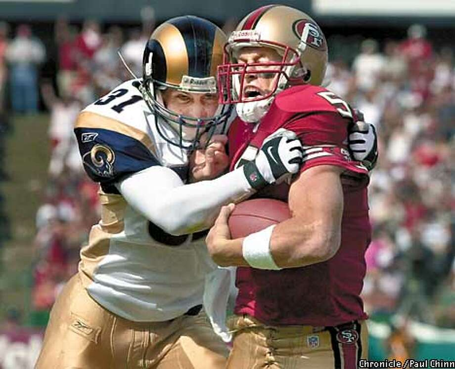 49ers quarterback Jeff Garcia comes under pressure from Rams Adam Archuleta as the San Francisco 49ers played the St. Louis Rams at 3Com Ballpark in San Francisco, Ca., on Sunday, September 23, 2001. (PAUL CHINN/SAN FRANCISCO CHRONICLE) Photo: PAUL CHINN