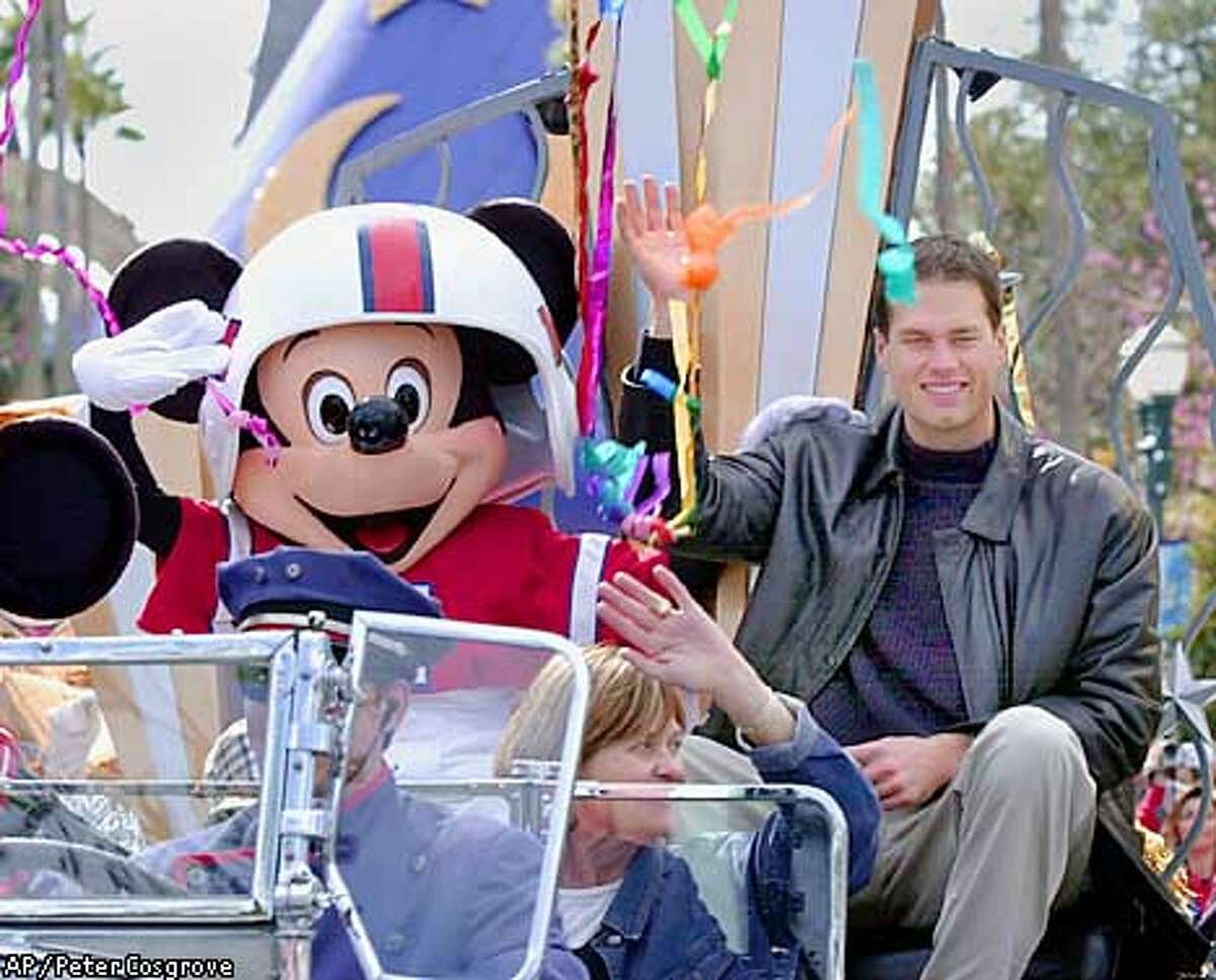 Super Bowl XXXVI most valuable player Tom Brady, Mickey Mouse and Brady's mother Galynn Brady, center, ride through falling streamers in a parade at Disney's MGM Studios in Lake Buena Vista, Fla. Monday, Feb. 4, 2002. Brady led the New England Patriots to an upset victory over the St. Louis Rams on Sunday. (AP Photo/Peter Cosgrove)