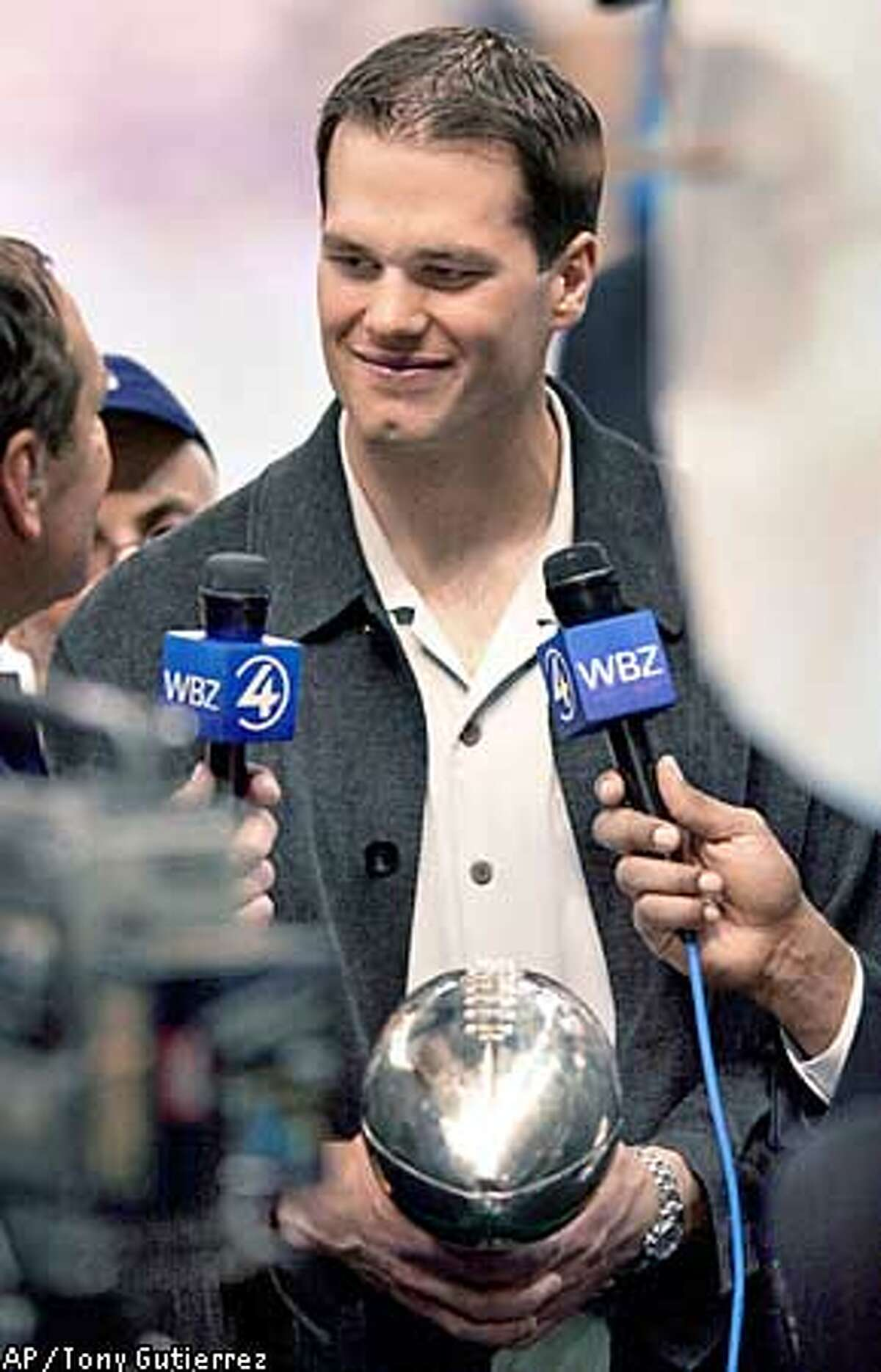 New England Patriots quarterback Tom Brady holds the Vince Lombardi Trophy as he is interviewed after the Patriots beat the St. Louis Rams 20-17 in XXXVI at the Louisiana Superdome Sunday, Feb. 3, 2002 in New Orleans. (AP Photo/Tony Gutierrez)