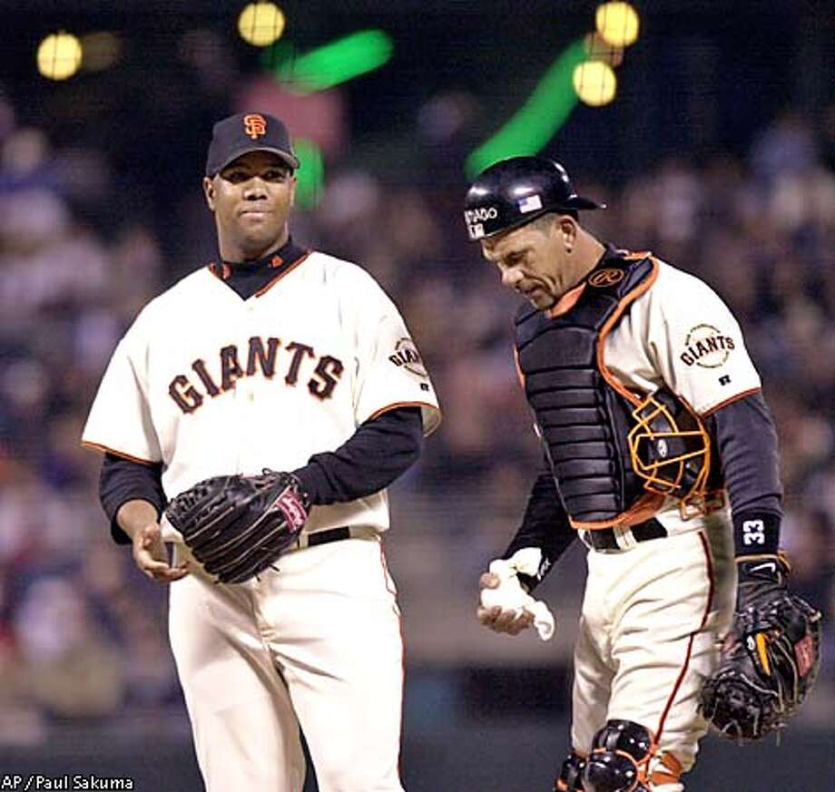 San Francisco Giants catcher Benito Santiago, right, talks with pitcher Livan Hernandez, left, on the mound after four Houston Astros players scored in the first inning, Wednesday, Sept. 19, 2001 in San Francisco. (AP Photo/Paul Sakuma) Photo: PAUL SAKUMA