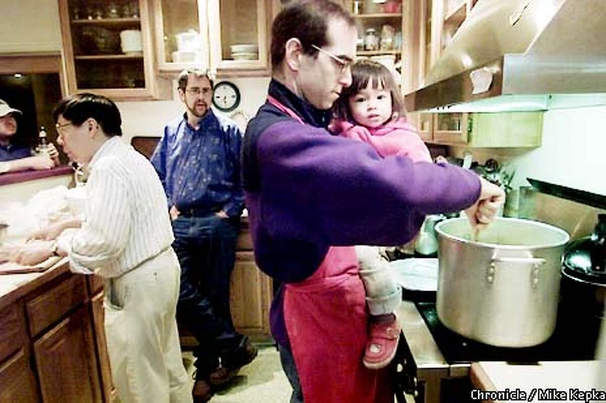 COHOUSING09a-C-02FEB02-HM-MK - With the help of Yorkrman Lowe(left), and Derek Cummings (middle), Barry Harris and his daghter Mina Nemoto Harris, 18 months, work on dinner for 19 at their cohouse in Emerville. The group takes turns making dinner three nights a week. BY MIKE KEPKA/THE CHRONICLE
