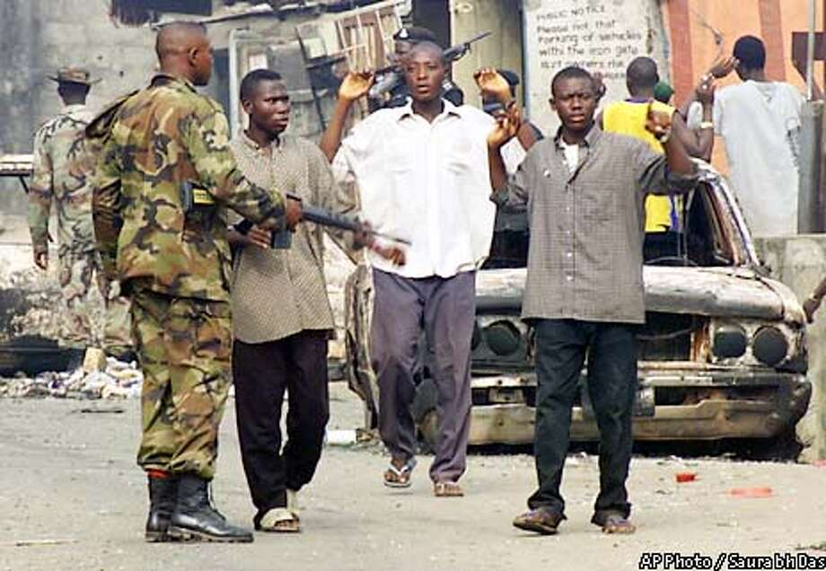 A soldier stops youths to find out if they belong to the area of the Idi Araba neighborhood in Lagos, Nigeria, Tuesday Feb. 5, 2002. Soldiers restored calm in the area which had witnessed violent fights between the ethnic communities of Hausas and Yorubas leading to the death of over 50 people. (AP Photo/Saurabh Das) Photo: SAURABH DAS