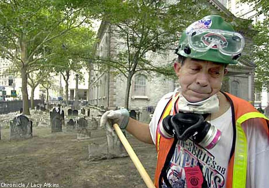 "Jay Agosdenho wept as he worked at cleaning ash and debris from the grounds of St. Paul's Chapel Episcopal Trinity Parish, established in 1766, which is in Manhattan, three blocks from the World Trade Center. ""I saw the people jump from the buildings,"" Agosdenho said. ""My heart feels sick; it doesn't feel good."" Chronicle photo by Lacy Atkins"
