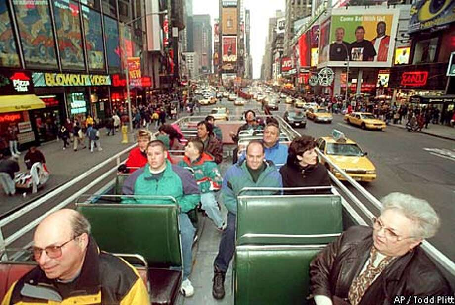 Tourists take advantage of unseasonably warm temperatures to ride on the upper deck of a tour bus through Times Square in New York, Saturday, Dec. 28, 1996. Temperatures in New York City reached into the 50s while the Pacific Northwest is being slapped by a winter storm. (AP Photo/Todd Plitt) Photo: TODD PLITT