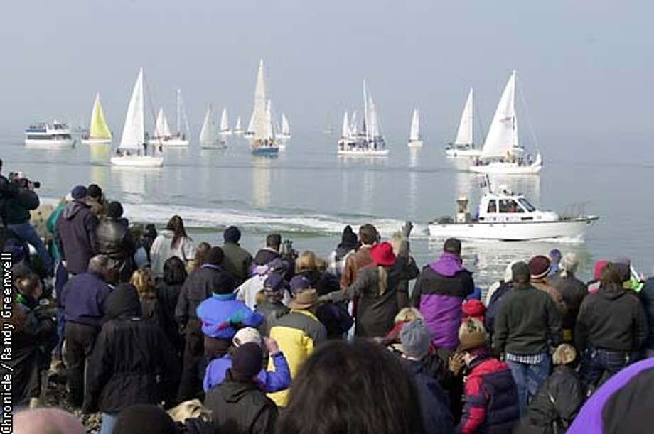 OLYMPICS07B-C-06FEB02-MN-RG Spectators gather along the southern shore of the Great Salt Lake as the Olympic cauldron is ushered across the water for a tour around Antelope Island before heading north towards Ogden Wednesday, February 6, 2002. The 2002 Winter Olympics takes place in Salt Lake City, Utah. Randy Greenwell/The Chronicle