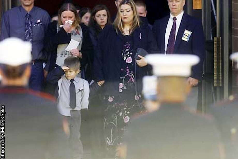 At St. John's Catholic Church in Napa, Alex Morgan, 4, takes a second to salute his fallen father, Marine, staff sgt. Dwight Morgan who was killed in a helicopter crash in Afghanistan. (his mother Teresa Morgan is to his immediate right in flower dress) BY MIKE KEPKA/THE CHRONICLE Photo: MIKE KEPKA