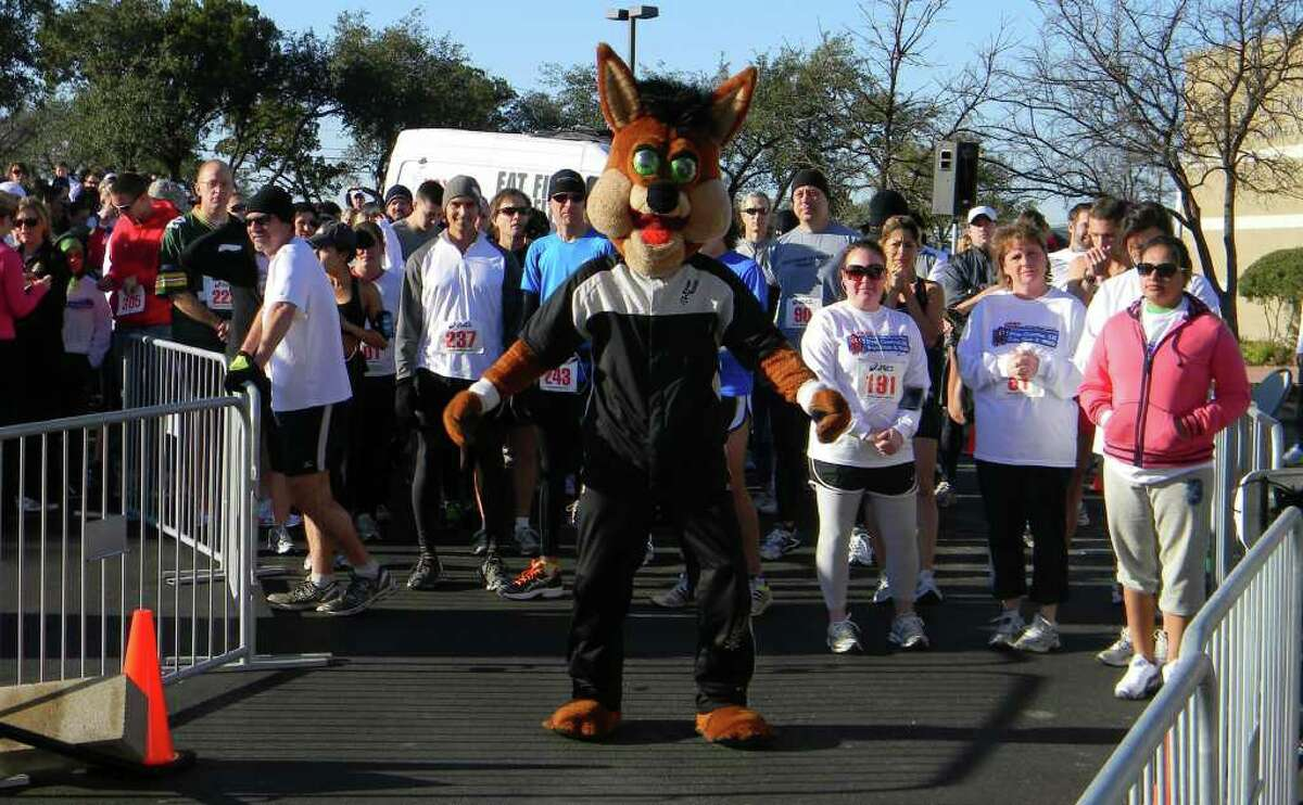 The Spurs Coyote with participants in the 2101 Super Bowl Sunday 5K run.