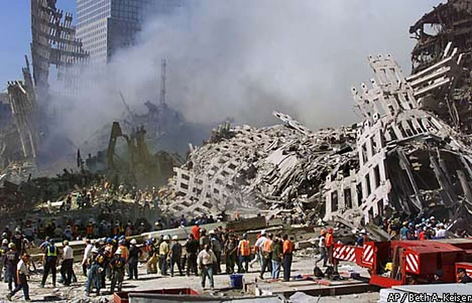 Rescue workers continue their search as smoke rises from the rubble of the World Trade Center, Thursday, Sept. 13, 2001, in New York. The search for survivors and the recovery of the victims continues since Tuesday's terrorist attack. (AP Photo/Beth A. Keiser) Photo: BETH A. KEISER
