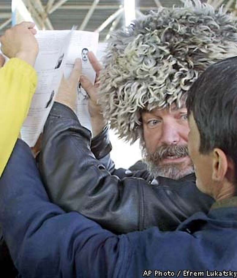 An American who calls himself Greg Shade shows fliers with pictures of eight al-Qaida leaders, including Osama bin Laden, to a local resident in Uzbek border town of Termez adjacent to Afghanistan Wednesday, Dec.19, 2001. Since October, Shade has been travelling through some of the remotest areas of Uzbekistan and Tajikistan giving local authoroties fliers with pictures of al-Qaida leaders and explanations of the massive U.S. rewards offered for them. Shade is on a one-man private mission in two formerSoviet republics to make sure al-Qaida leaders do not escape justice. (AP Photo/Efrem Lukatsky)