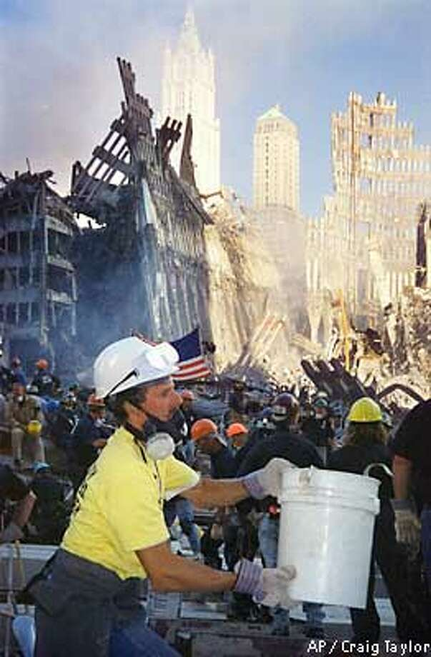 An unidentified volunteer works in a bucket line Saturday, Sept. 15, 2001 in New York, to remove rubble from ground zero at the World Trade Center, scene of the terrorist attack on Tuesday. As exhausted rescue workers clawed through the wreckage of the World Trade Center, searching for signs of life four days after the terrorist attacks, financial experts declared Wall Street ready for at least a semblance of business Monday. (AP Photo/Craig Taylor) Photo: CRAIG TAYLOR