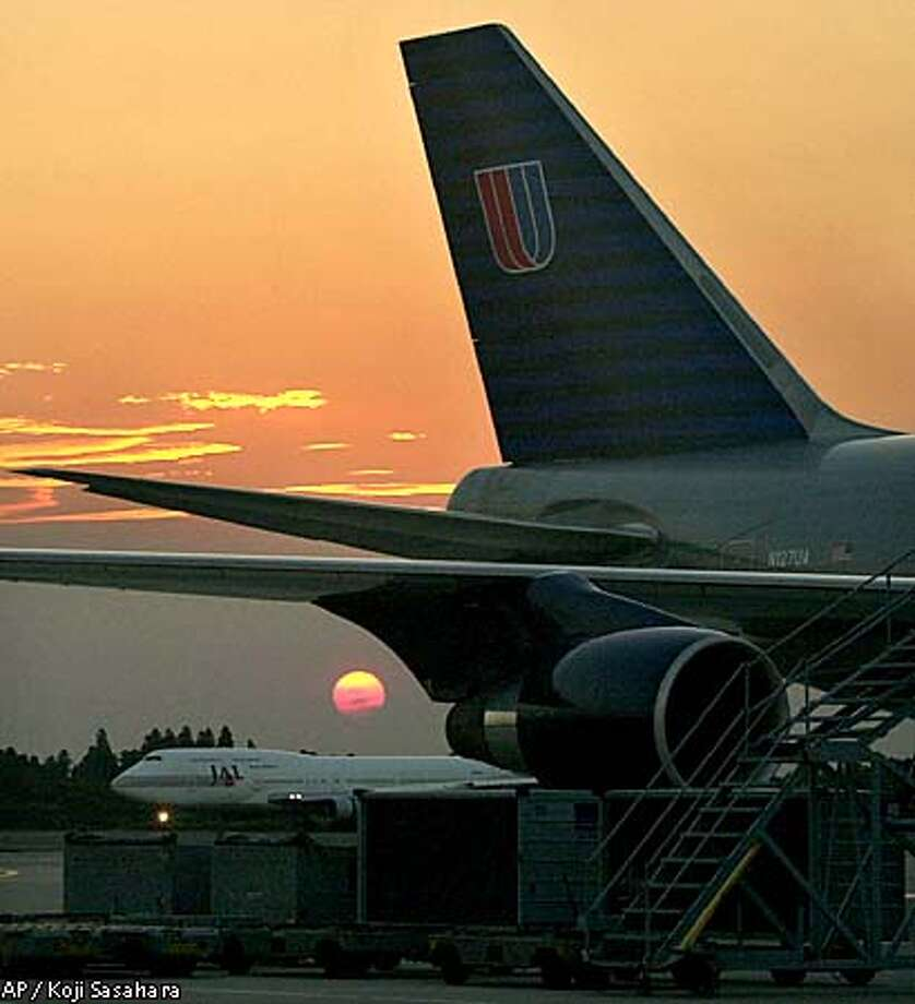 A United Airlines jetliner sits on the tarmac at New Tokyo International Airport in Narita, east of Tokyo, at sunset Wednesday, Sept. 12, 2001, as all flights bound for the United States are cancelled following the terrorist attacks on New York City and Washington. (AP Photo/Koji Sasahara) Photo: KOJI SASAHARA