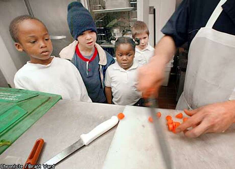 Students from Starr King Elementary School watched food preparer Louis Cameron cut carrots at the Asqew Grill on Steiner Street in San Francisco recently. The kindergarten class of Andrew Jenkins toured the restaurant and had lunch as part of a relationship between the school and the restaurant to show students the inner workings of the cafe. By Brant Ward/Chronicle Photo: BRANT WARD