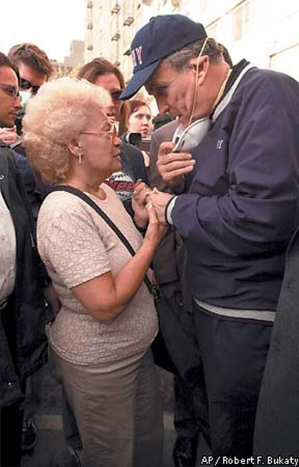 "New York City Mayor Rudolph Giuliani consoles Anita Deblase, of New York, whose son, James Deblase, 44, is missing, at the site of the World Trade Center disaster, Wednesday, Sept. 12, 2001. ""He's at the bottom of the rubble,"" she said. James Deblase worked for Cantor Fitzgerald at the World Trade Center. (AP Photo/Robert F. Bukaty) Photo: ROBERT F. BUKATY"