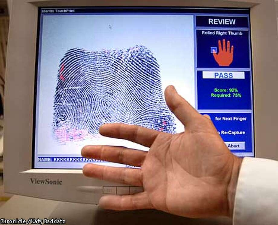 Photo by Katy Raddatz--The Chronicle  Identix, Inc. is a company specializing in fingerprint reading technology. SHOWN: The TouchPrint 2000 Job Applicant System, providing forensic quality print reading. Reporter is Benny Evangelista. Photo: KATY RADDATZ