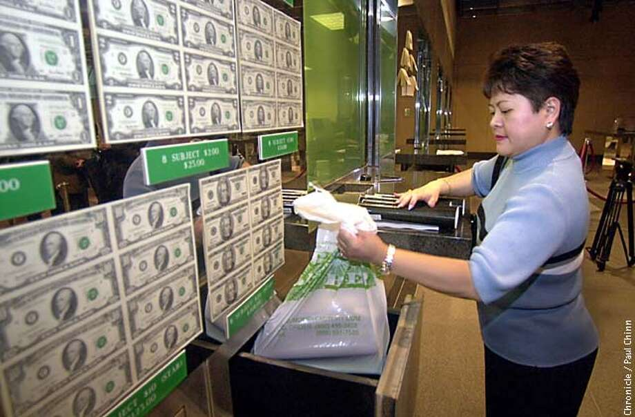 Fe Martinez gathered up shopping bags filled with 53 collectable sets she just purchased. The Department of Treasury made sheets of U.S. currency available to purchase in a rare public sale at the Federal Reserve Bank downtown  PAUL CHINN/S.F. CHRONICLE Photo: PAUL CHINN