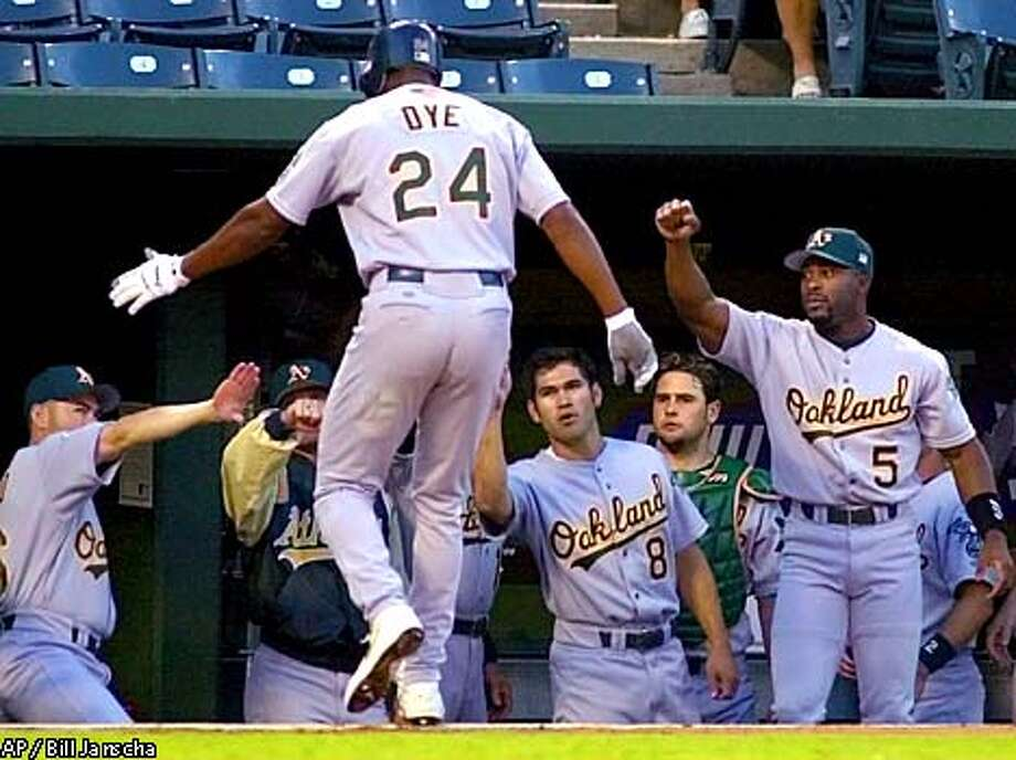 Oakland Athletics' Jermaine Dye (24) receives congratulations from teammates, including Johnny Damon (8) and Ron Gant (5), after his first-inning sacrifice fly that scored Miguel Tejada against the Texas Rangers in Arlington, Texas, Thursday, Sept. 20, 2001. (AP Photo/Bill Janscha) Photo: BILL JANSCHA