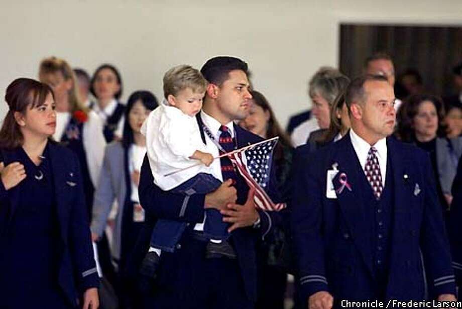 : Hundreds of United and American Airlines pilots, flight attendance and ground crew personnel held a memorial service at SFO for their colleagues that were killed Sept 11 from terrorism. Both American Airlines flight attendants Kenneth Faria (center) and his wife Mary (far left) brought his son Shea (2) (with the flag) to the service, no name of the person on the right. Chronicle photo by Frederic Larson Photo: FREDERIC LARSON