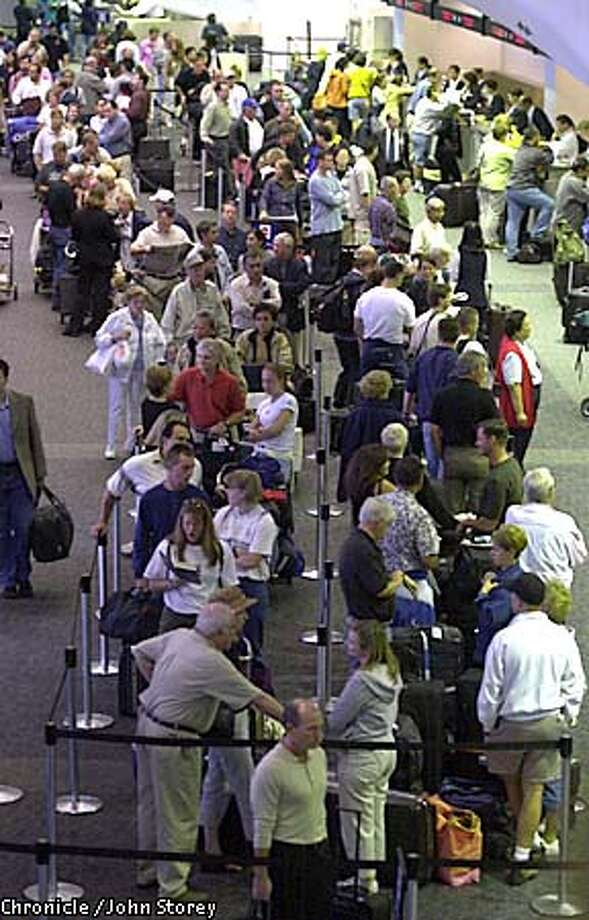 AIRPORT-C-14AUG01-MN-JRS-Huge crowds wait at SFO for flights to leave. Also tighter security measures in place at the airport.Passengers wait at the North Terminal for flights on American Airlines. Chronicle Photo by John Storey. Photo: John Storey