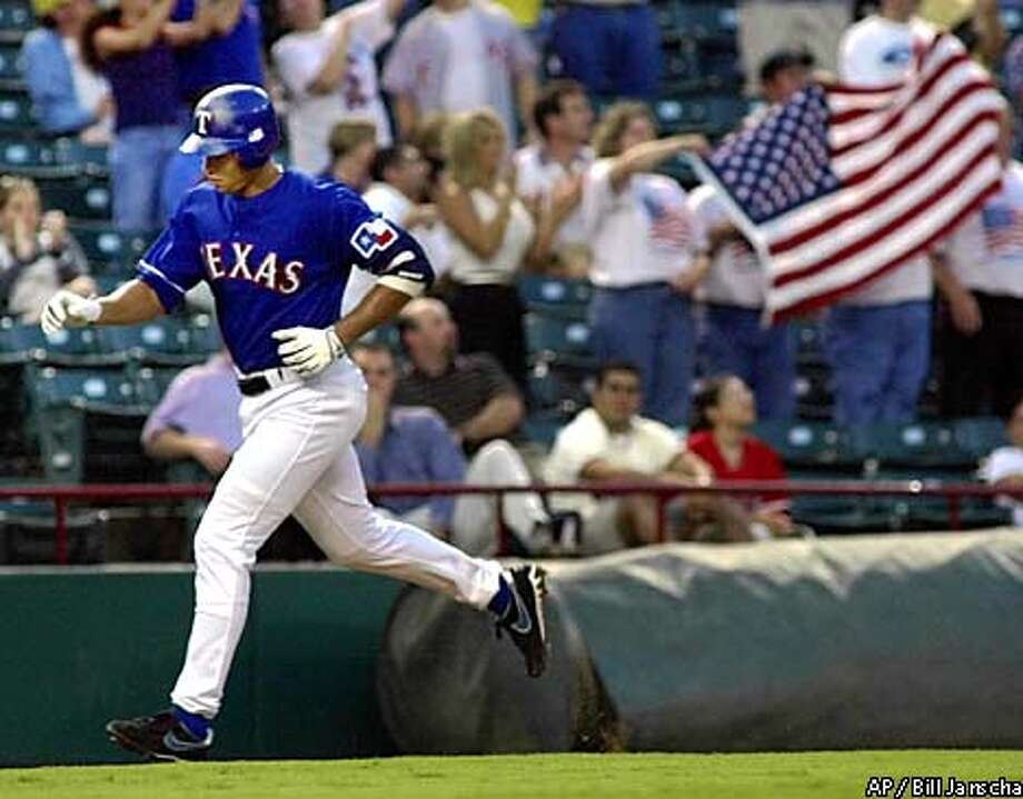 Texas Rangers' Alex Rodriguez runs toward home plate past fans waving a large American flag during the first inning after he hit a two-run home run against the Oakland Athletics in Arlington, Texas, Wednesday, Sept. 19, 2001. The home run was Rodriguez's 46th home run of the season. His next home run this season will tie Ernie Banks for the major league record of home runs hit by a shortstop in a season. (AP Photo/Bill Janscha) Photo: BILL JANSCHA