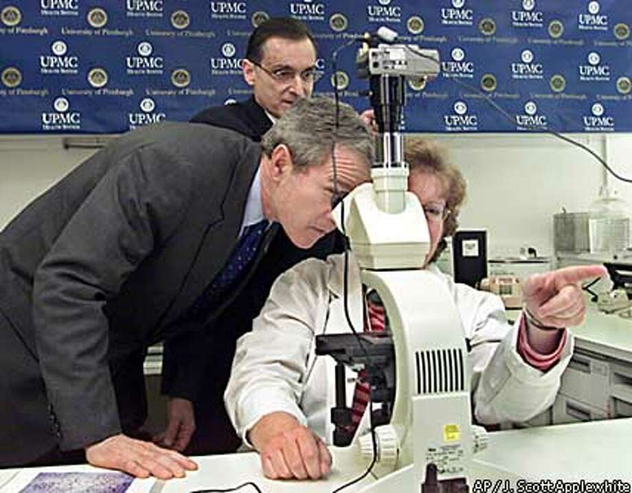 President Bush looked at anthrax through a microscope during a tour of a lab at the University of Pittsburgh Medical Center. Associated Press photo by J. Scott Applewhite