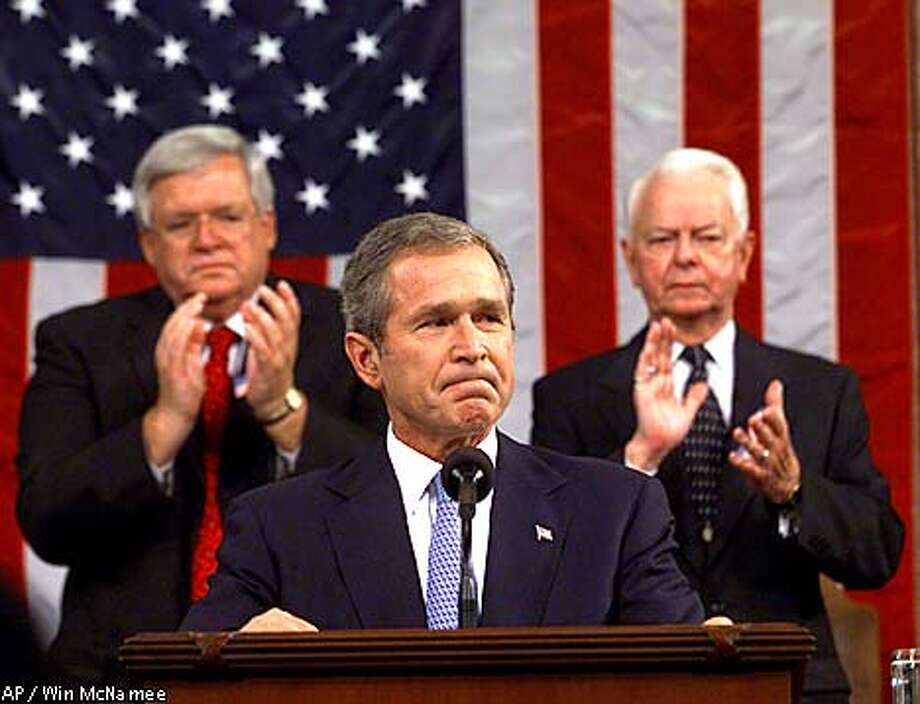 As U.S. troops and warplanes move into position, President Bush addresses a Joint Session of Congress on Capitol Hill, to prepare Americans for a long, deadly and often covert war against the elusive terrorists, Thursday, Sept. 20, 2001. Sitting behind Bush are Sen. Robert Byrd, D-W.Va., president pro-tem of the Senate, and House Speaker Dennis Hastert, R-Ill., left. (AP Photo/ Win McNamee, Pool) Photo: WIN MCNAMEE