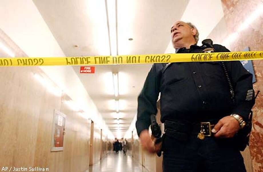 San Francisco police officer Gary Constantine stands guard over a hallway at the Hall of Justice where a moderate explosion occured in a first floor men's bathroom on Wednesday Feb. 6, 2002, in San Francisco. Police spokesman Sherman Ackerson said the explosion occured at 12:35 pm. Ackerson says it could have been something as small as a firecracker or something more sophisticated. The building, which houses courtrooms and police headquarters, was briefly evacuated while bomb squads conducted a sweep.(AP Photo/Justin Sullivan) Photo: JUSTIN SULLIVAN