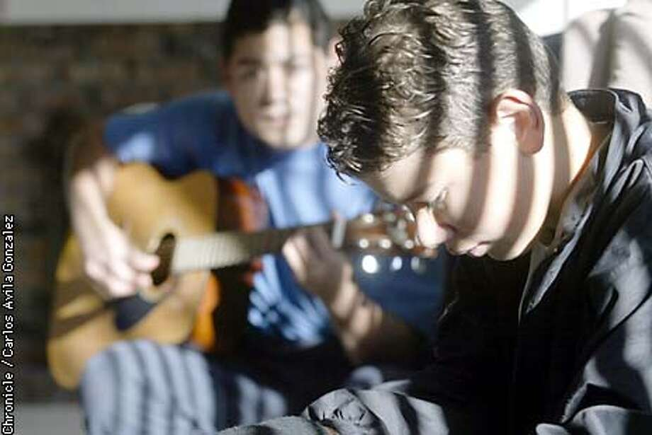 Manuel Romero, 12, prepares to sing a spanish ballad while his father, Manuel plays the guitar in their home in Milpitas on Wednesday, 23, 2002. The young singing sensation is only twelve, and has sung for many groups and organizations, and has been signed by Warner Music Latina. He has been singing since he was 8 years old.  (CARLOS AVILA GONZALEZ/SAN FRANCISCO CHRONICLE) Photo: CARLOS AVILA GONZALEZ