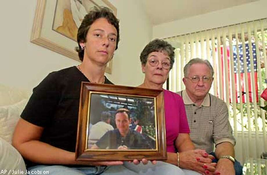 Darlene Keohane, left, sits with her parents, Mary and Donald Keohane, while holding a portrait of her brother, John Keohane, Monday, Sept. 17, 2001, in Pacifica, Calif. John Keohane, 41, was evacuated from his office building near the World Trade Center during the terrorist attacks Tuesday, Sept. 11, 2001, and was killed a few blocks away when the buildings collapsed. (AP Photo/Julie Jacobson) Photo: JULIE JACOBSON