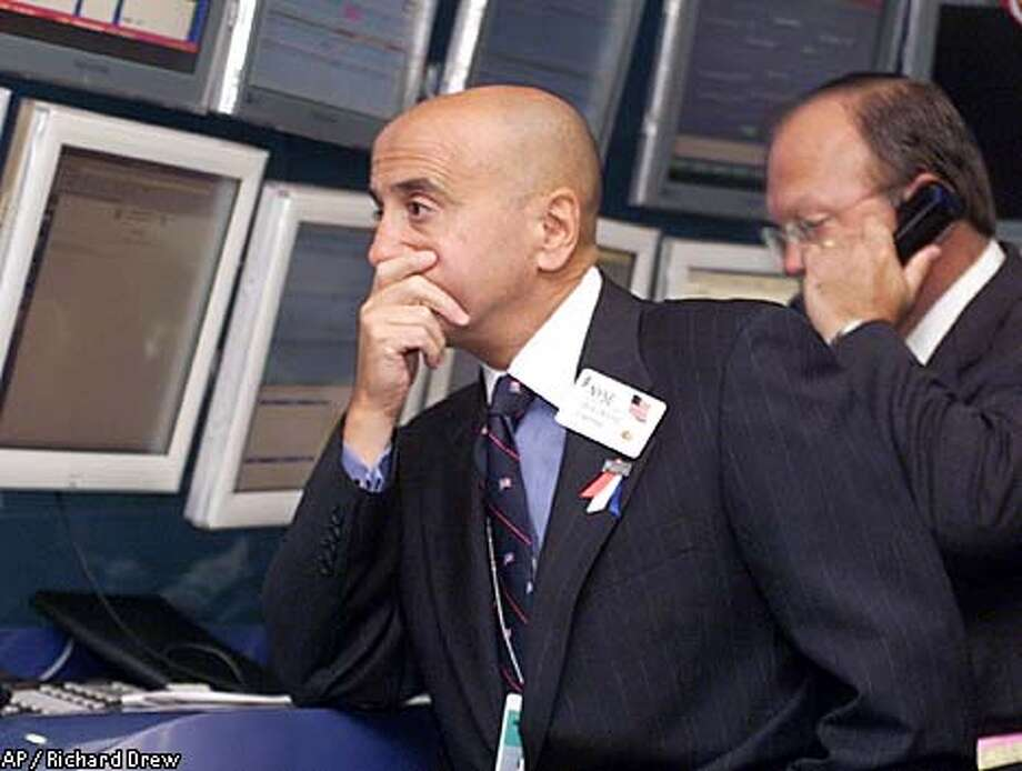 New York Stock Exchange Chairman Richard Grasso, left, rests his chin in his hand as he visits the trading floor's operations center before the opening of trading Tuesday, Sept. 18, 2001. Investors looked to Tuesday's session on Wall Street with apprehension, fearing further damage to the stock market from the terror attacks. (AP Photo/Richard Drew) Photo: RICHARD DREW