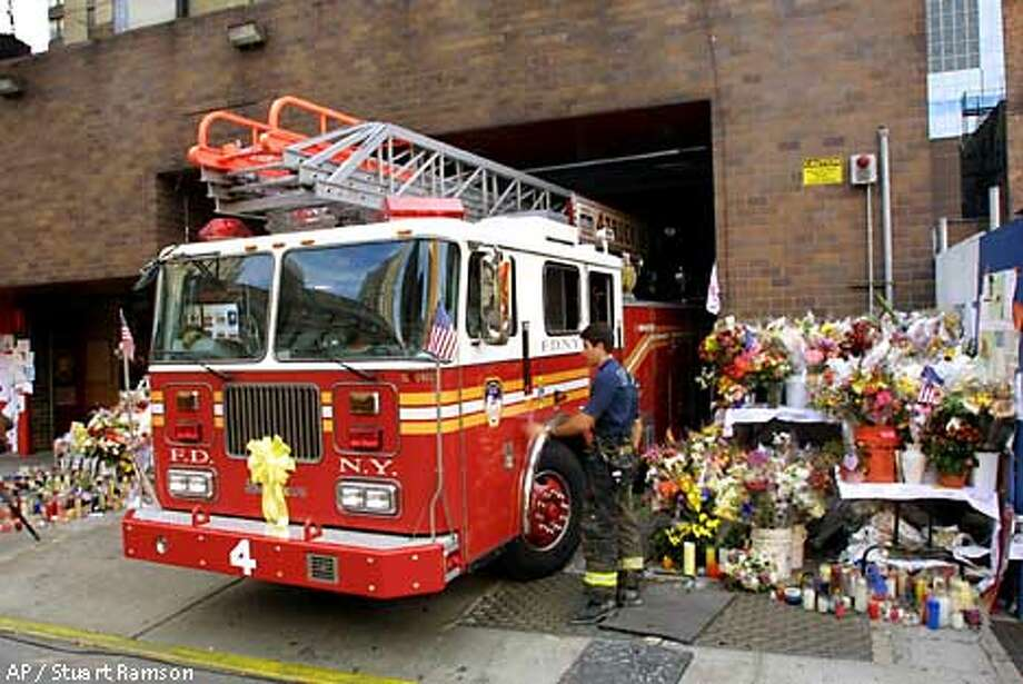 Ladder 4 truck is surrounded by makeshift memorials as it returns to its midtown New York firehouse after a call Tuesday, Sept. 18, 2001, one week after the terrorist attacks against the World Trade Center. This single firehouse lost 15 men when the twin towers collapsed. (AP Photo/Stuart Ramson) Photo: STUART RAMSON