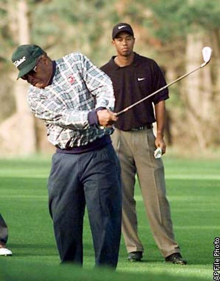 Earl Woods hits from the fairway on the eighth hole of the Spyglass Hill Golf Course as his son Tiger Woods looks on during a practice round in Pebble Beach, Calif., Tuesday Jan. 27, 1998. The pair will play together as a team when the AT&T Pebble Beach National Pro-Am begins on Thursday.(AP Photo/Eric Risberg) Photo: ERIC RISBERG