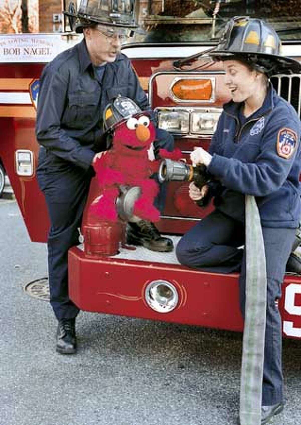 NYC firefighters comfort Ernie after he witnesses a fire at Hooper's Store in opening episode of Sesame Street. HANDOUT.