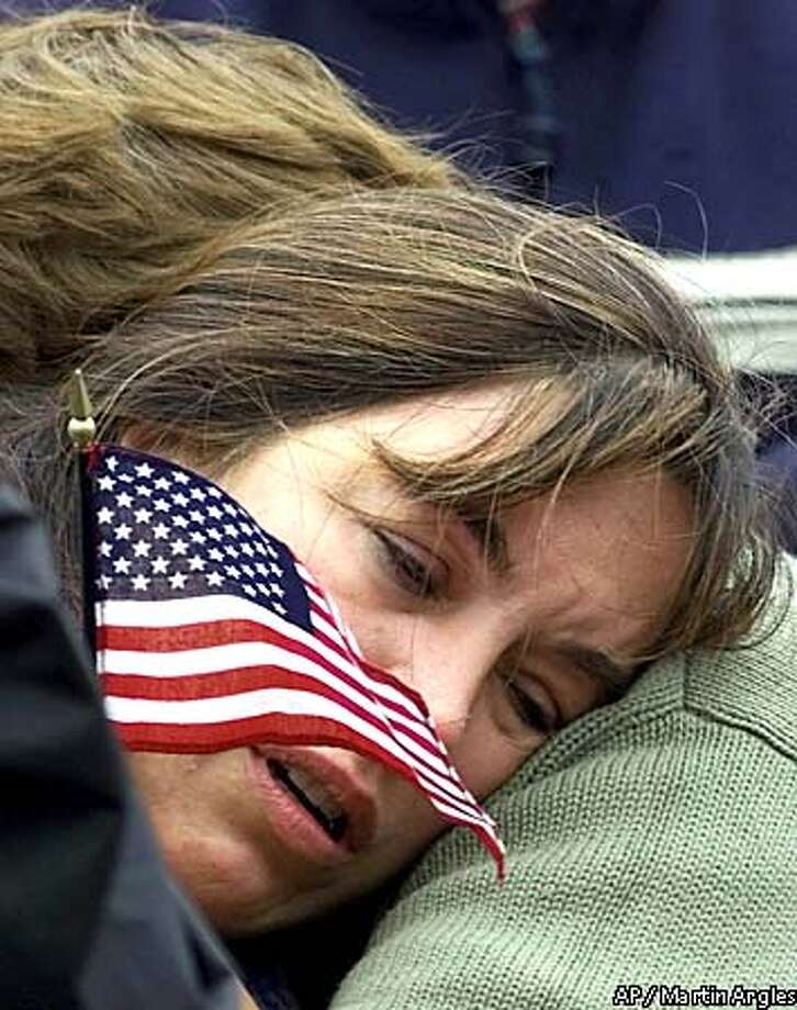 Mourners, one holding the American flag, console one another during the playing of the United States national anthem by the Coldstream Guards, at London's Buckingham Palace Thursday, Sept. 13, 2001, during a special changing of the guard ordered by Britain's Queen Elizabeth to honor victims of the Tuesday's terrorist attacks in the United States. (AP Photo/Martin Argles/Courtesy The Guardian) UNITED KINGDOM OUT Photo: MARTIN ARGLES