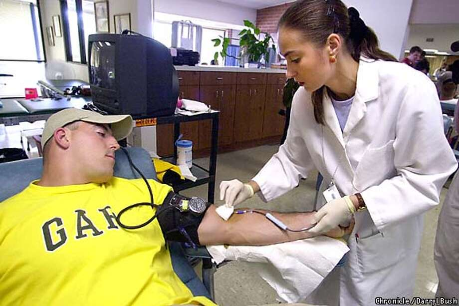 49ers' David Fiore is tended to by phlebotomist by Anna Asovskaya at Pacific Blood Centers in Burlingame. The entire 49er team gave blood at the center in part to help rescue efforts of Americans harmed in recent terrorist attacks. Chronicle Photo by Darryl Bush Photo: Darryl Bush