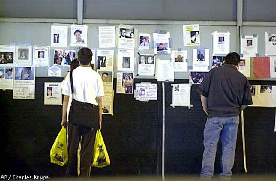Pictures posted by family and friends showing people missing following Tuesday's terrorist attack on the World Trade Center hang on a wall at the New York University Hospital, Thursday, Sept. 13, 2001, in New York. (AP Photo/Charles Krupa) Photo: CHARLES KRUPA