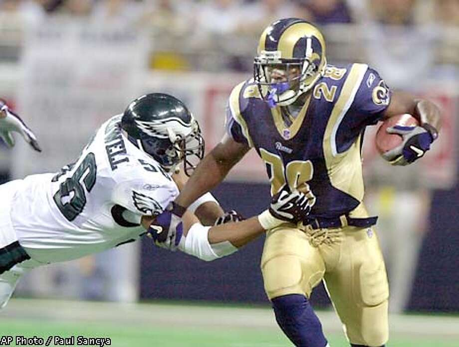 Philadelphia Eagles' Mike Caldwell (56) tries to tackle St. Louis Rams running back Marshall Faulk (28) in the second quarter of the game Sunday, Jan. 27, 2002 in St. Louis. (AP Photo/Paul Sancya) Photo: PAUL SANCYA