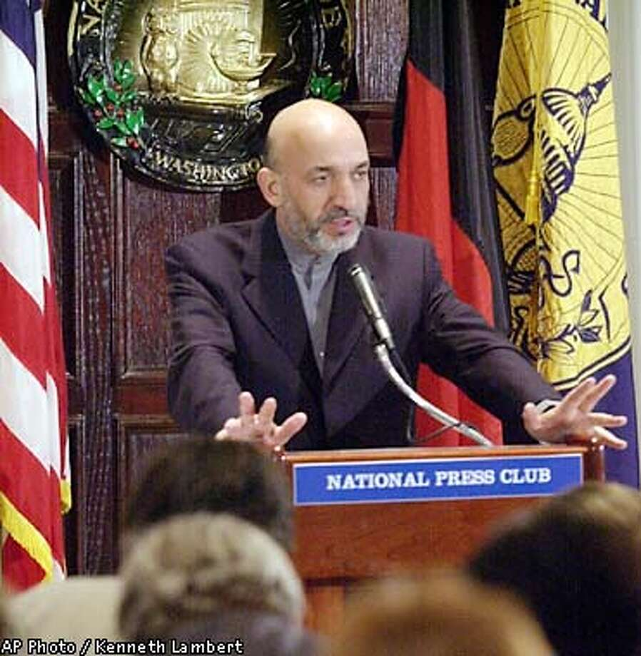 Interim Afgahn leader Hamid Karzai gestures while addressing a luncheon at the National Press Club in Washington Tuesday, Jan. 29, 2002. Karzai said democracy will thrive in his country and elections will be held in two years. (AP Photo/Kenneth Lambert) Photo: KENNETH LAMBERT