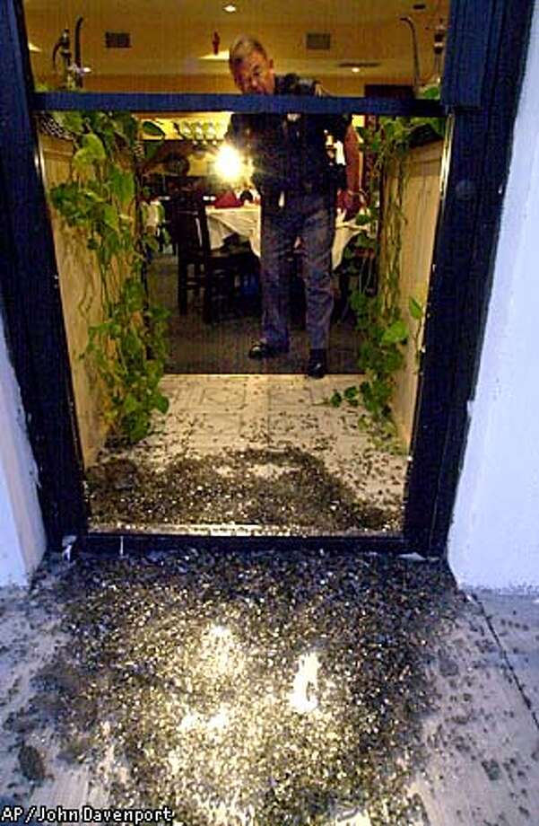 "Olmos Park, Texas Police officer Ruben Aldaz shines his flashlight through a glass door that was shot out with a ball-bearing from a sling-shot , at Shiraz Restaurant Thursday Sept. 13, 2001. Police there said someone called the dispatcher's office claiming the act was ""payback for New York."" Shiraz is a town in Iran. (AP Photo/San Antonio Express-News, John Davenport) Photo: JOHN DAVENPORT"